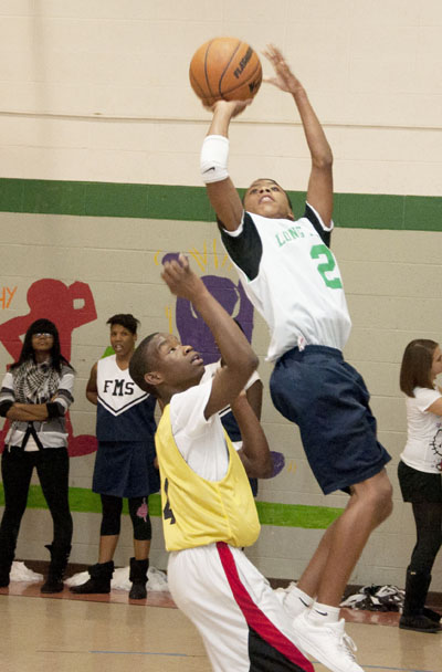 A Long Middle School student shoots a jumper over a Fanning Middle School defender during a tough and competitive game.